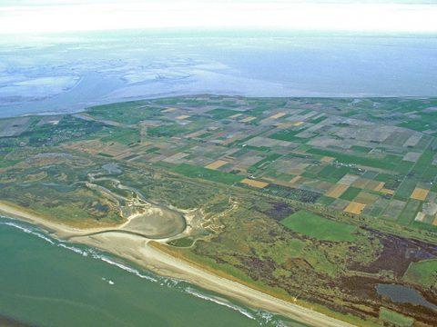 Luchtfoto van de noordelijke helft van Texel, met de Noordzee, de Slufter, de Muy, de polder Eijerland en daarachter het wad. Foto: foto Fitis