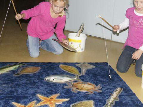 Twee meisjes hengelen naar houten vissen