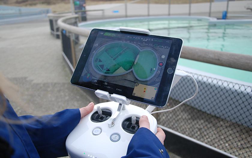 Twee handen houden het scherm vast waarop de beelden van de drone te zien zijn
