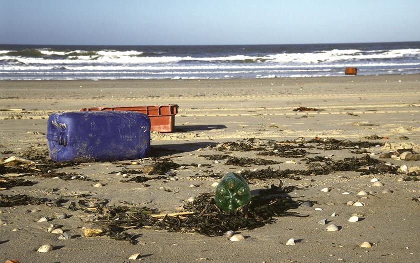 Zwerfvuil in het vloedmerk op strand